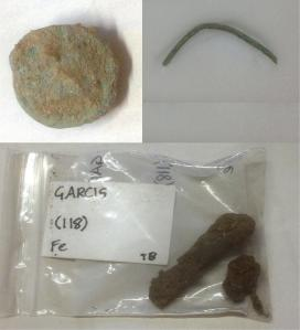 Clockwise from top-left: Roman coin, possible hairpin/broach-pin and corroded iron nail
