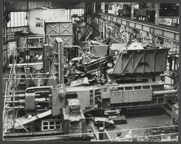Photograph of Scrap metal bailing press in operation