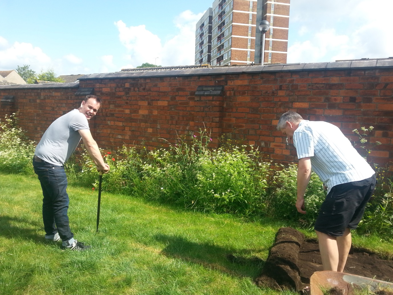 Image of Mark and Richard, two of our volunteers braving the heat to pull up the turf!